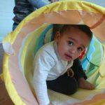 Baby boy crawling through tunnel