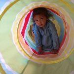 Baby girl crawling through tunnel