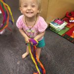 Baby girl dancing with ribbon wands