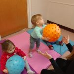 Babies learning ball passing and catching skills