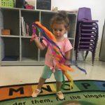 Toddler girl dancing with ribbon wand