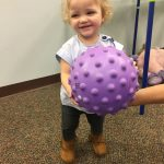 Baby girl learning ball skills