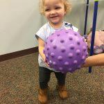 Baby girl learning ball skills