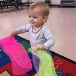 Baby girl dancing with scarves